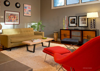 Mid-Century Modern furniture and an eclectic mix of art and vintage hubcaps make for a lively sitting room.