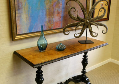 An antique console table visually grounds the more contemporary art on the same wall.