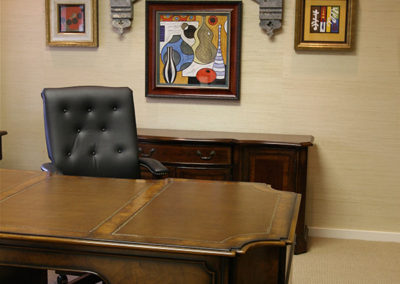 An antique architectural fragment paired with contemporary paintings creates an interesting backdrop to this law office.