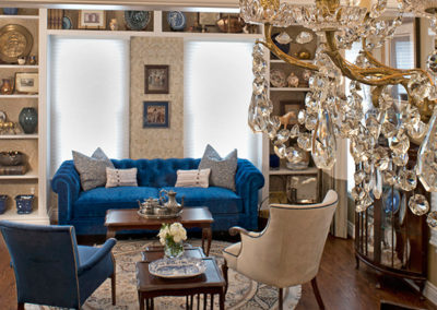 A bold blue Chesterfield sofa nestled between the built-ins makes for a cozy tea room in this Welsh-inspired home.
