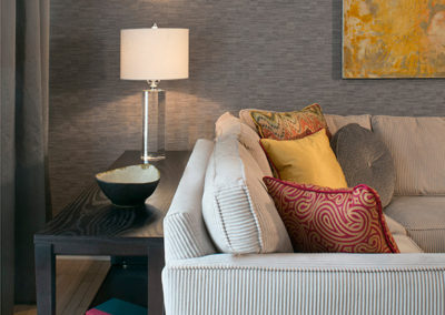 These clients wanted their sitting area to have more of a lounge feel; so Dan Davis Design implemented textured wallpaper, sconces, and custom drapery all done in subdued colors to reach this relaxing effect.