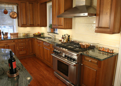 Copper accents and warm cherry cabinets are accentuated by a granite in colors of sage and black.
