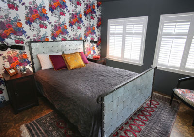 Bold in a small space?  Of course!  Floral and Industrial?  Of course!  Light and dark?  Of course!  This small bedroom takes all of the so-called design rules and turns them on their head.  We took an over the top floral wallpaper and paired it with an industrial metal bed.  Dark grey walls and ceiling are balanced by large windows with white shutters.  Masculine and feminine are completely disregarded by placing them both in the same room at the same time and creating a genderless space.