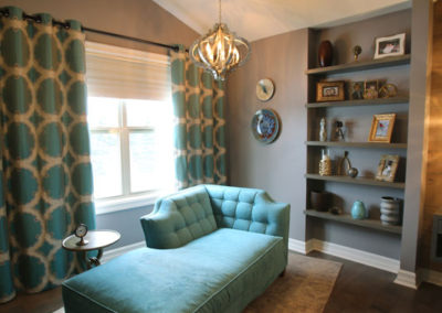 A reading area in this master bedroom, pops with custom drapery, a velvet turquoise chaise and a Moroccan-inspired chandelier.