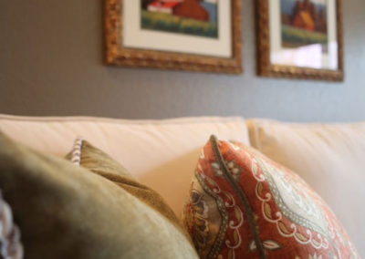 Custom pillows and original farm-themed artwork tie the colors<br />of the room together.