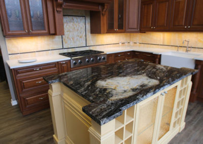 To bring some punch to this showroom display kitchen, an eye-catching granite was selected to go on top of a contrast island in an unexpected color.  The onyx back splash ties in nicely with the buttery color of the island.