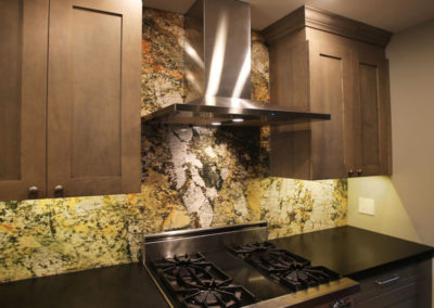 This galley kitchen wall features an exotic granite backsplash with black granite countertops. Custom lighting was incorporated to properly illuminate the granite backsplash.