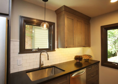 This galley kitchen wall features crackle-glazed subway tile, glass pendant, and black granite countertops