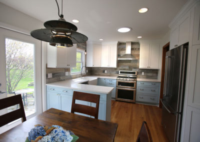 The barn wood style tile, sink, and powder blue cabinets set the pace for the farmhouse style of this kitchen. Stainless steel appliances and industrial touches keep it from feeling too precious.