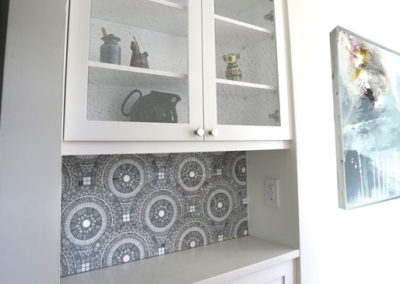 This existing alcove was reimagined as a bar with new shimmery backsplash tile and glass upper cabinetry to open the space.