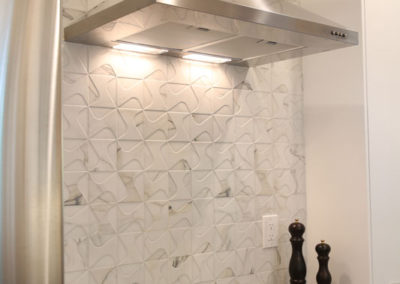 A unique Italian dimensional porcelain tile adds texture and height to the space.