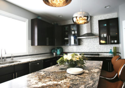 To add visual interest to this kitchen, we specified two different granites; a simple one for the perimeter and a showstopper for the waterfall island.  The addition of the capiz shell tile backsplash and mirrored light fixtures create glamorous yet functional touches.
