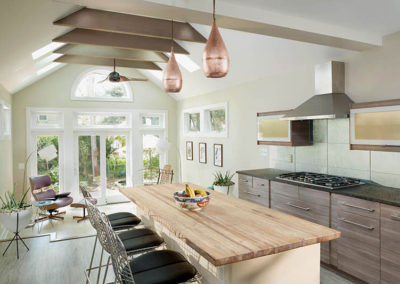 A kitchen/addition tripled the size of the old kitchen and accommodated a sunroom. Custom cabinets and cork flooring add interest and the copper pendants are a nice juxtaposition to the cooler colors of the backsplash.