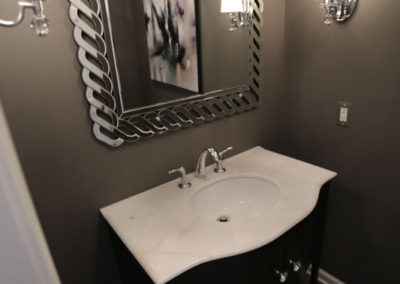A small powder room that is not small on glamour.  For that wow factor we selected a curved vanity, sconces with glass finials, and a unique mirror; together they add up to create big impact.