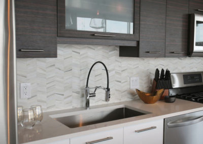 Backsplash tile is laid in a herringbone pattern. Subtle grays in the tile pick up the stainless steel tones.