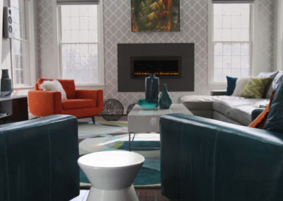 A space like this requires scale and color.  We gave both to our clients with the bold orange and teal chairs, the large graphic pattern of the wallcovering, and the oversized piece of commissioned artwork.