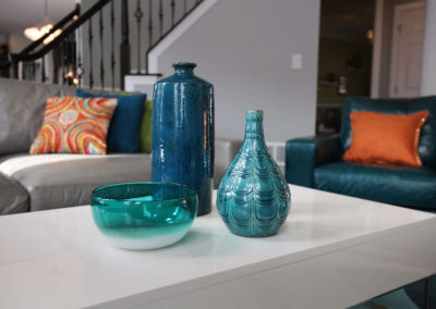 One of the easiest and most affordable ways to add color and texture to a monochromatic room is with accessories and pillows.  We did just that with these ceramic vases, colored glass bowl, and the graphic pillows.