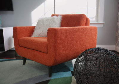 Warm orange accents, including this Mid-Century Modern inspired chair, balance the cooler grays and blues. Texture is added with a wire sculpture, faux fur pillow, and ceramic pottery.