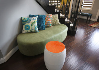 A custom-made ottoman snugs neatly in the nook allowing for a spot to take shoes on-and-off at the front door. Pillows, a rug, and drum table add color.