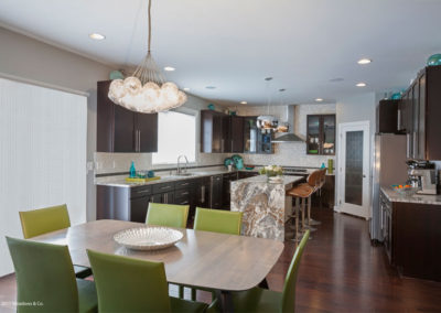 This kitchen and dining area sing with colorful accessories, green dining chairs, and the visual texture of the waterfall island.  These all add an unexpected twist to a neutral back drop of the cabinets and backsplash and create a more personalized space.