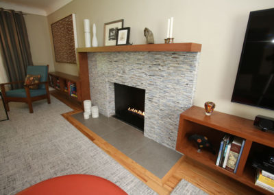 The dilemma of a long, narrow living space was solved with the unique design of integrated built-ins and fireplace mantle and a custom rug notched around the hearth.