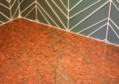 We chose Red Dragon granite for the countertops. A soft-turquoise glass backsplash picks up on the same color flecks in the granite.