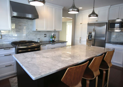 Custom cabinets, marble countertops, marble backsplash, and new lighting were brought in. The small-scale island was replaced with this multi-functional piece positioned for maximum space.