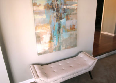 Art and accessories are always needed to finish off a room and make it feel complete.  Here we used a single large scale piece of art coupled with a versatile bench to create a space that looks put together and inviting.