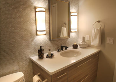 A master bath with no windows needed to feel light and airy. Shimmering tiles and a floating vanity add to the look. And these sconces are both beautiful as well as functional.
