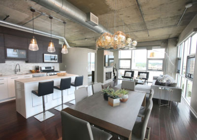 """A loft with a """"builder's special"""" look was completely customized. Horizontal grain in the new upper cabinetry and white lowers with a waterfall counter on the island lend to the contemporary feel."""