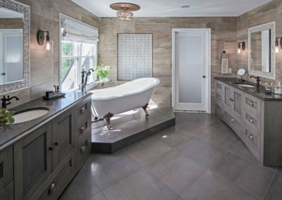 A his and her bathroom we designed with engraved marble accent tile, bronze metals and a raised soaking tub for a better view of the gardens.