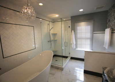 We removed a walled-in shower and outdated tile  in this renovation of a master bath. The new space is calm, classic and also luxurious with finishing touches of wallpaper, a sculptural tub and a crystal chandelier.