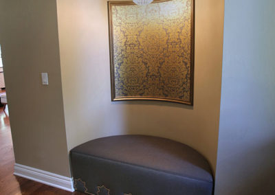 Our clients newly purchased home had an art niche in the foyer.  But no place for a bench to sit on for taking off your shoes.  A custom ottoman, decorative wallpaper and well-appointed lighting make this feature both functional and wonderful.