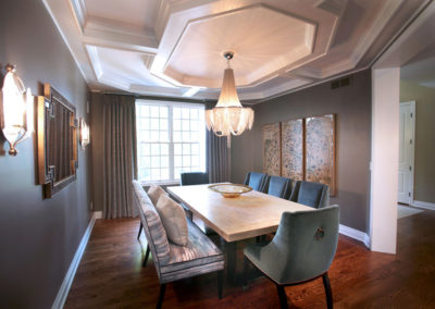 What was an outdated and plain dining room takes an updated glamourous turn with architectural details, dramatic lighting and beautiful furnishings.
